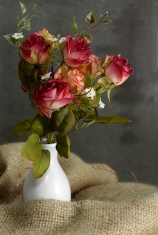 Natureza morta com flor rosa em vaso branco sobre pano de saco