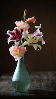 Natureza morta com flores do verão em um vaso no escuro