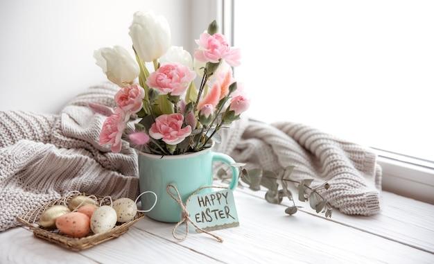 Natureza morta com flores frescas da primavera em um vaso, ovos, um cartão de feliz páscoa e um elemento de malha.