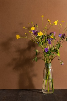 Natureza morta com flores silvestres em frasco de vidro em fundo marrom. composição moderna e moderna com flores secas, sombras escuras vista lateral