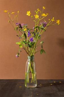 Natureza morta com flores silvestres em frasco de vidro na composição da moda moderna de fundo marrom com secado ...