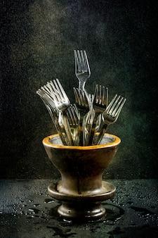 Natureza morta com garfos em um vaso sob irrigação por gotejamento