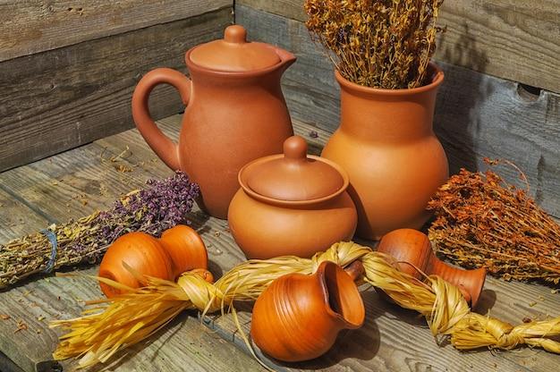 Natureza morta com jarros de barro de vários tamanhos e feixes de ervas medicinais secas em uma velha mesa de madeira.