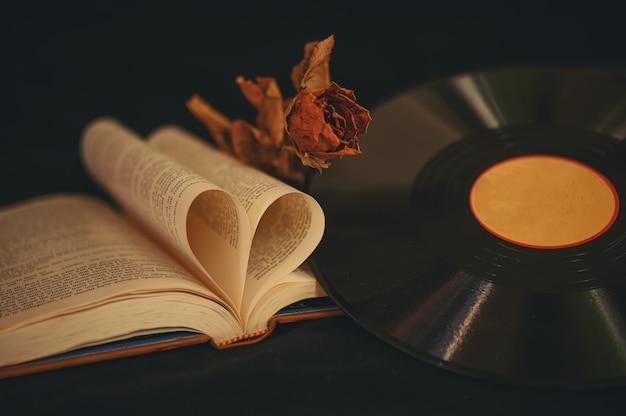 Natureza morta com livros em forma de coração, flores secas e cd antigo.