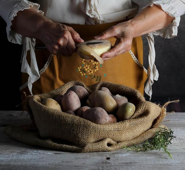 Natureza morta com mãos de mulher descascando batatas novas