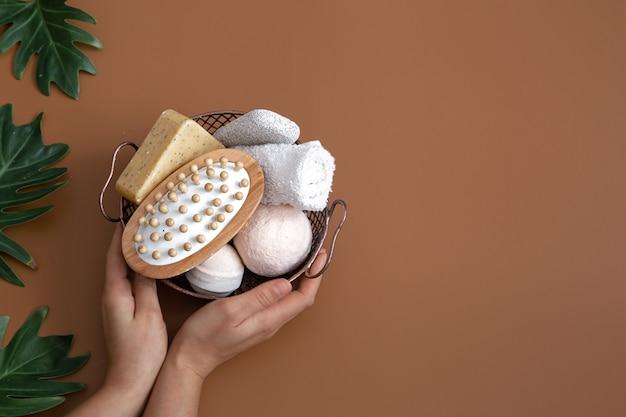 Natureza morta com mãos femininas, escova de massagem, bombas de banho, sabonete e uma toalha em uma cesta com vista superior de folhas.