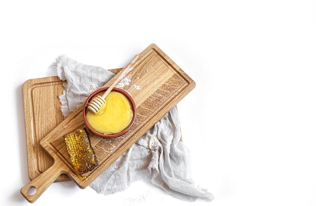Natureza morta com mel natural e favo de mel em uma prancha de madeira fechar isolado.