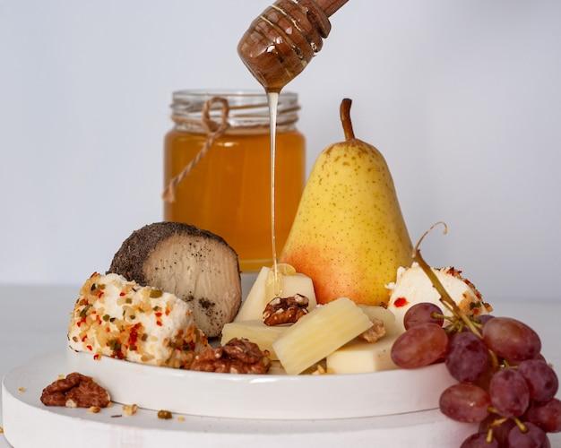 Natureza morta com mel uvas, pêssegos e queijo