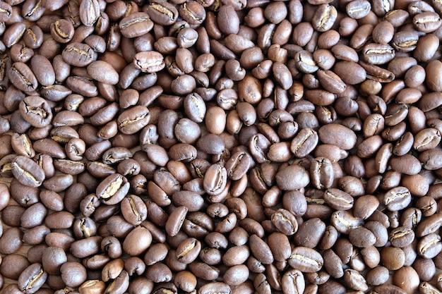 Natureza morta com muitos grãos de café torrados espalhados como plano de fundo vista de cima de perto