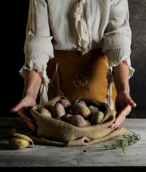 Natureza morta com mulher mostrando saco com batatas sobre a mesa