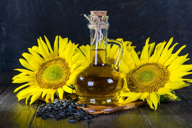Natureza morta com óleo de girassol em frasco de vidro, sementes e girassol