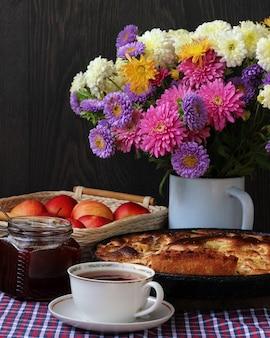 Natureza morta com outono buquê de crisântemos, chá e torta de maçã.