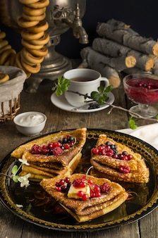 Natureza morta com panquecas ucranianas e russas tradicionais para o feriado de maslenitsa com manteiga e frutas vermelhas em uma bandeja preta com um samovar