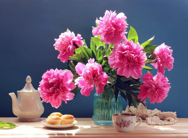 Natureza morta com peônias, bolos e bule. peônias de jardim-de-rosa em um buquê.