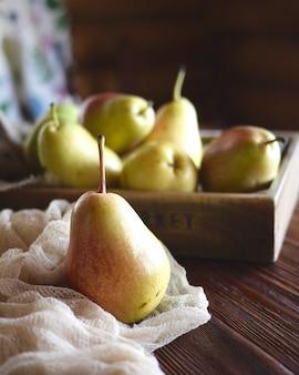 Natureza morta com peras frescas na mesa de madeira. luz baixa