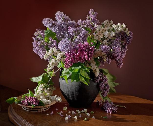 Natureza morta com ramos florescendo de lilás e tulipas em uma jarra de barro sobre uma mesa de madeira.