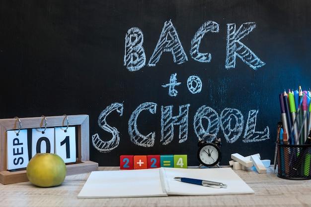 Natureza morta com relógio, material de escrita, um livro e uma maçã contra o quadro-negro com texto de volta às aulas.