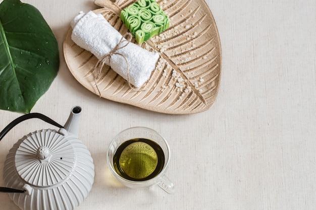 Natureza morta com sabonete, toalha, folha e espaço da cópia do chá verde. conceito de saúde e beleza.