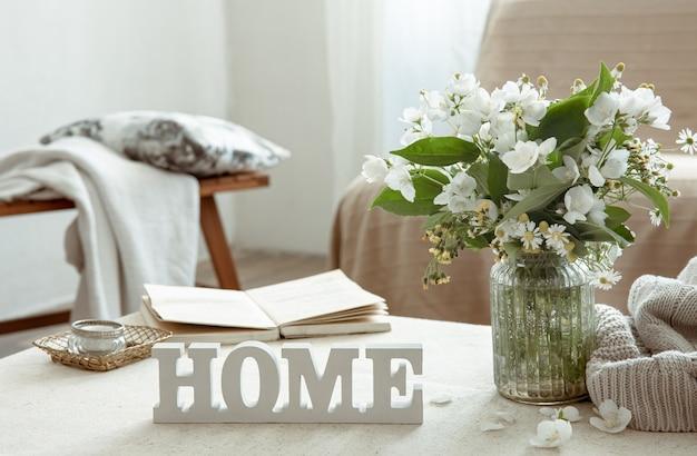 Natureza morta com um buquê de flores, um livro e uma palavra decorativa de madeira para casa.