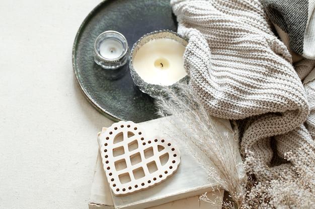 Natureza morta com um coração decorativo, livros e velas em castiçais. o conceito de dia dos namorados e a decoração da casa.