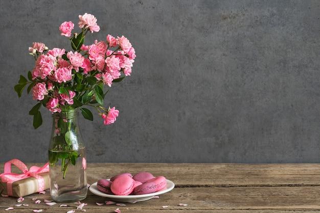 Natureza morta com um lindo buquê de flores rosas, macarons e caixa de presente.