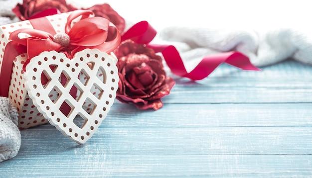 Natureza morta com um presente e um coração decorativo de madeira close-up. conceito de celebração do dia dos namorados.