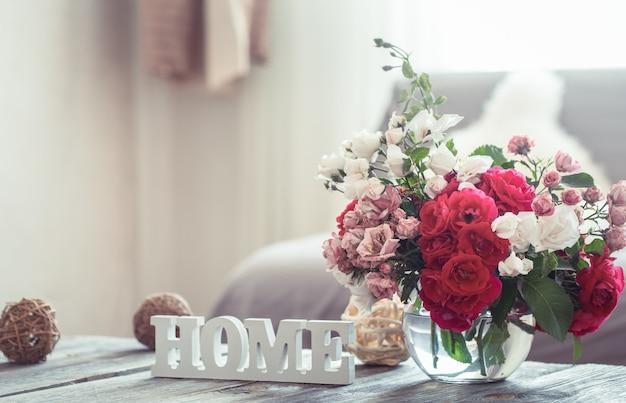Natureza morta com uma casa de inscrição e um vaso com flores de rosas diferentes. o conceito de conforto e decoração do lar.