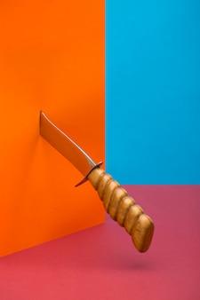 Natureza morta com uma faca afiada perfurando um objeto laranja