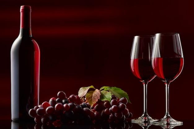 Natureza morta com uma garrafa de vinho tinto, taças e uvas. fundo preto e vermelho.