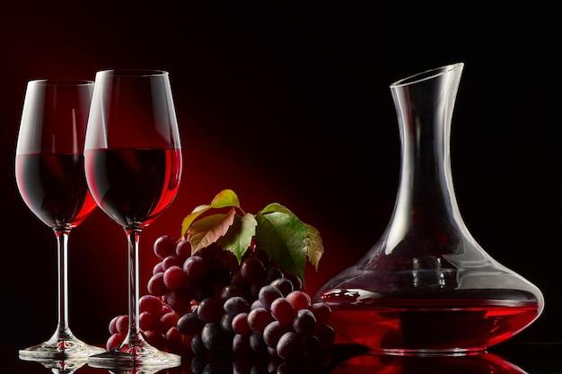 Natureza morta com uma garrafa de vinho tinto, taças e uvas.