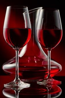 Natureza morta com uma garrafa e dois copos de vinho tinto em um glos