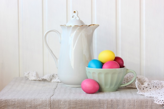 Natureza morta com uma jarra branca e ovos coloridos.