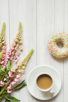 Natureza morta com uma xícara de café e flores de lupine donut em uma mesa de madeira clara