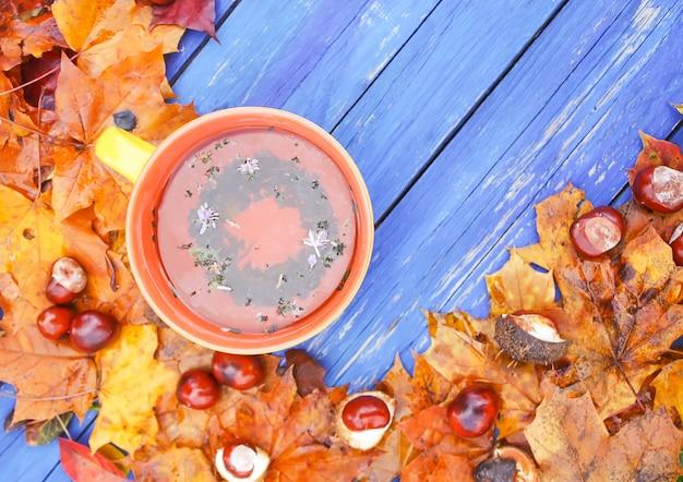 Natureza morta com uma xícara de chá, castanhas da índia e folhas de outono em placas de madeira azuis no jardim outono.
