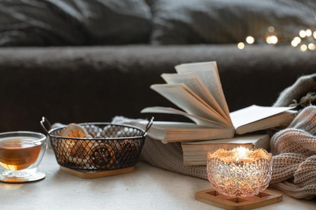 Natureza morta com uma xícara de chá, livros e uma vela acesa em um lindo castiçal. conceito de conforto em casa.