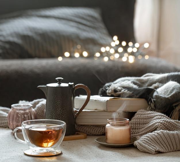 Natureza morta com uma xícara de chá, um bule, livros e uma vela em um castiçal em um fundo desfocado com bokeh.