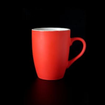 Natureza morta com xícara de chá de porcelana vermelha alta ou xícara de café dentro de casa, foto isolada em fundo preto vista frontal close-up