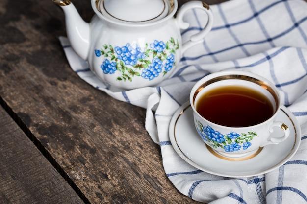 Natureza morta com xícara de chá e toalha de mesa na mesa de madeira