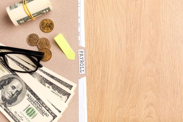 Natureza morta da folha de pagamento com vista superior de dinheiro e moedas