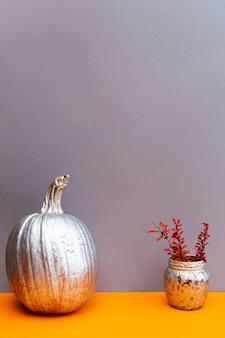 Natureza morta de abóbora dourada e raminhos rosa-laranja de bérberis em uma mesa cinza-laranja