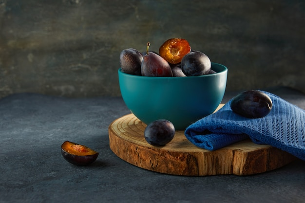 Natureza morta de ameixas em uma placa azul e um guardanapo em um suporte de madeira.