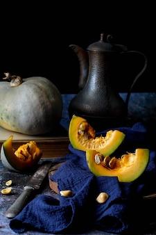 Natureza morta de comida de outono com abóbora fatiada e jarro vintage com pano de algodão azul