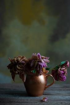 Natureza morta de flores murchas em um vaso de cobre, sobre uma mesa de madeira, contra um fundo abstrato quente de uma parede texturizada.