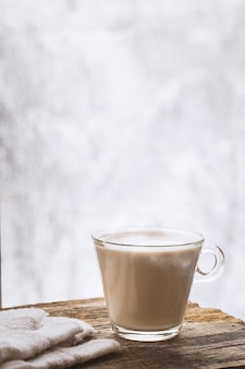 Natureza morta de inverno aconchegante: xícara de café quente e luvas quentes na mesa de madeira contra o fundo de árvores cobertas de neve fora da janela