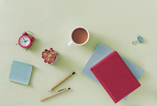 Natureza morta de negócios ou de escritório com caderno ou diário aberto em um fundo verde claro com caneta, lápis, flor, caneca de café e clipe de papel em uma vista aérea