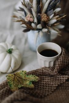 Natureza morta de outono com uma xícara de café com flores e abóboras em uma manta aconchegante