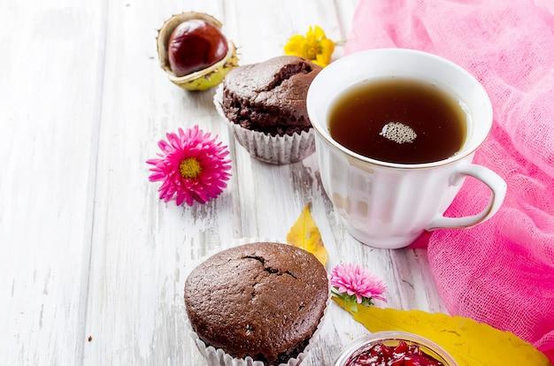 Natureza morta de outono com uma xícara de chá, biscoitos e folhas no conceito de fundo de madeira branco