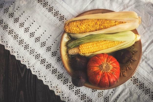 Natureza morta de outono em estilo rústico com abóbora, milho e figos em uma toalha de mesa branca com renda
