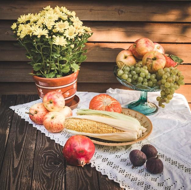 Natureza morta de outono em estilo rústico com maçãs, abóbora e milho, romã e figos em uma toalha de mesa branca com renda e flores amarelas de crisântemo