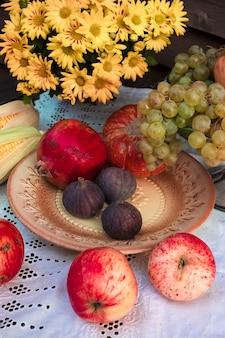 Natureza morta de outono em estilo rústico com maçãs, romãs e figos em uma toalha de mesa branca com renda e flores amarelas de crisântemo